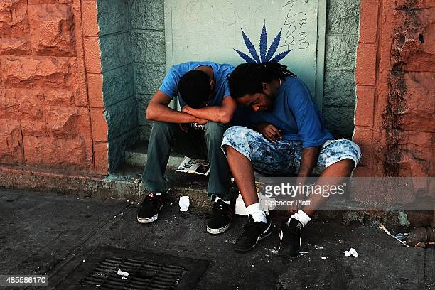 Two men who are high on K2 or 'Spice' a synthetic marijuana drug sleep along a street in East Harlem on August 28 2015 in New York City New York...