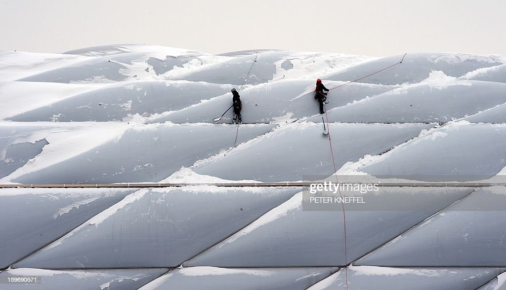 Two men with climbing gear and equipment remove snow from the bright plastic shell of the Allianz Arena on January 18, 2013 in Munich, southern Germany. AFP PHOTO / PETER KNEFFEL /GERMANY OUT