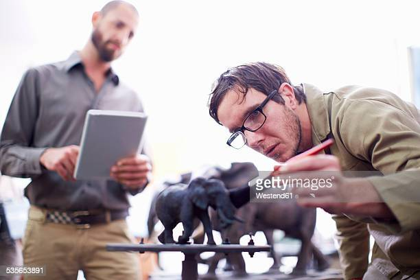 Two men with digital tablet in a sculptors workshop