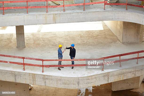 Two men with hard hats clinking beer bottles on construction site