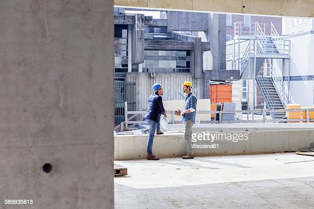Two men with hard hats talking on construction site