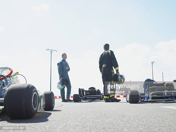 Two men with helmets standing near go-carts, rear view
