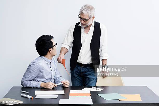 Two men with markers and papers talking