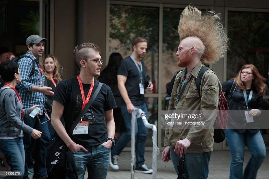 CONTENT] Two men with mohawk hairstyles converse on the sidewalk in Austin, Texas during the SXSW Interactive 2013 conference