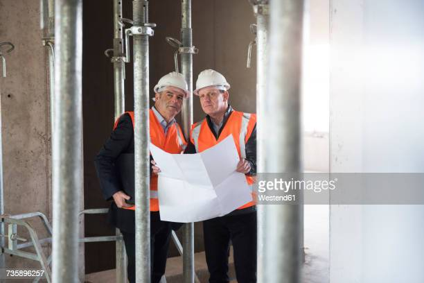 Two men with plan wearing safety vests in building under construction