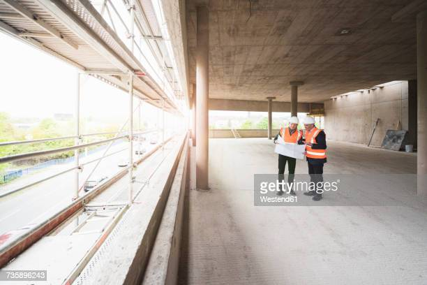 Two men with plan wearing safety vests talking in building under construction