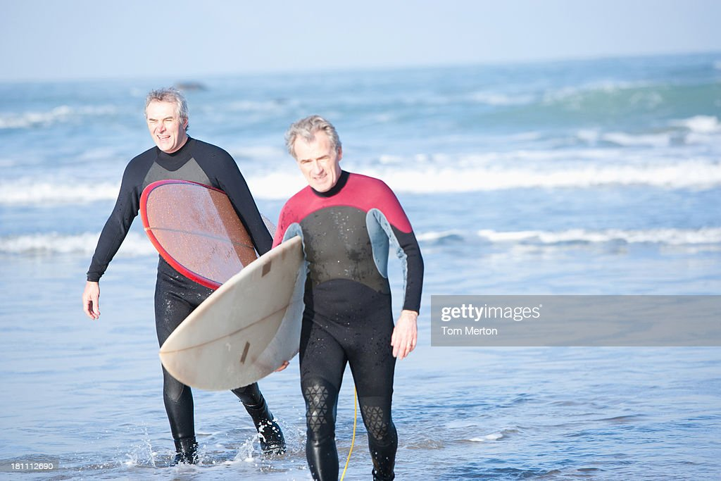 Two men with surfboards running into the water : Stock Photo