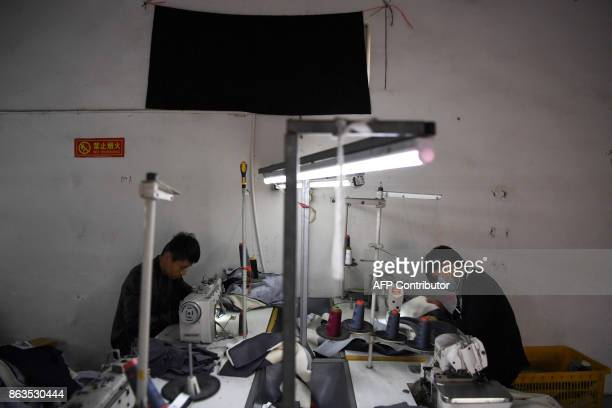 Two men work in a clothing factory on the outskirts of Beijing on October 20 2017 China's economy slowed marginally in the third quarter but is well...