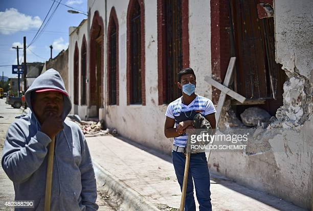 Two men work on July 30 2015 in the site where a truck plowed into a crowd of pilgrims in Mazapil Zacatecas State northcentral Mexico The truck...