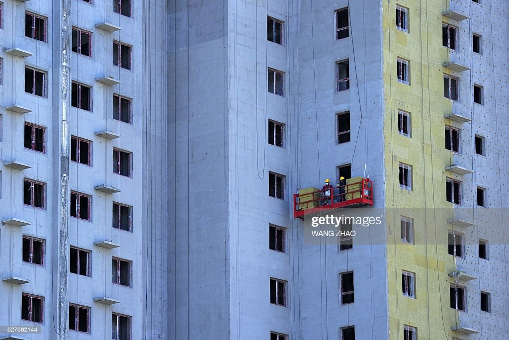 Two men work on the exterior of a building at a construction site in Beijing on May 3, 2016. China's economic recovery stabilished in April, an official factory activity gauge showed on May 1, as the property market recovered and credit grew. / AFP / WANG
