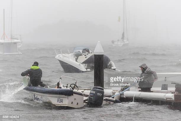 Two men work to save their boat from sinking during wild weather on June 5 2016 in Sydney Australia The Bureau of Meteorology is forecasting up to...