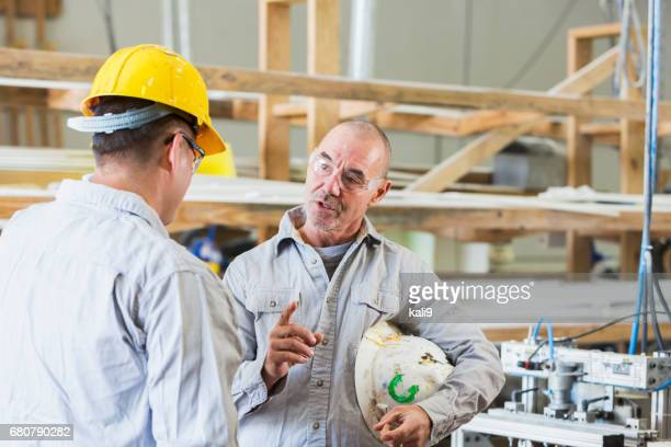 Two men working in a small factory,  serious discussion