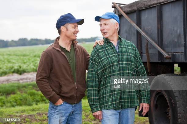 Two men working on a farm, talking by a truck