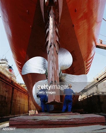 Two men working on propeller of ship on dry dock : ストックフォト
