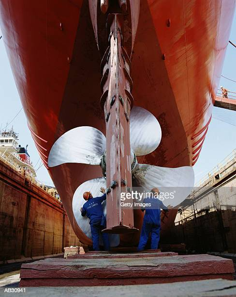 Two men working on propeller of ship on dry dock