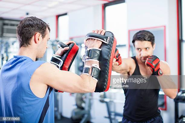 Two men working out punches in gym
