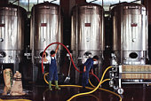 Two men working with metal wine fermentation vats
