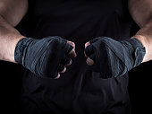 two men's hands wrapped in a black bandage, close up