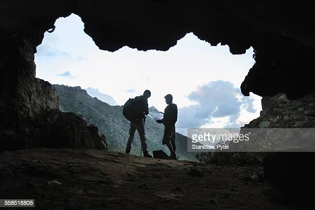 Two mens looking at map in mountains, view from ca