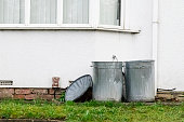 Two metal dustbins outside a house