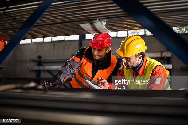 Two metal workers working together in aluminum mill.