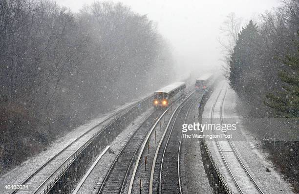 Two metro trains pass each other between Takoma and Silver Spring as snow revisits the region on January 2014