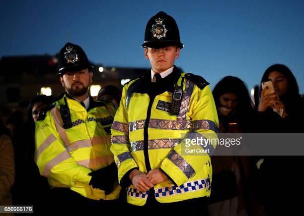 Two Metropolitan Police officers look on during a candlelit vigil at Trafalgar Square on March 23 2017 in London England Four People were killed in...