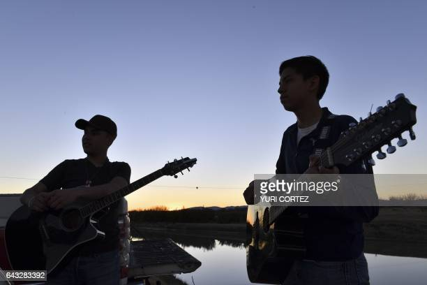 Two Mexican boys play guitars along the bank of Rio Bravo the natural border between US/Mexico in Ojinaga Mexico on February 20 north of Mexico...