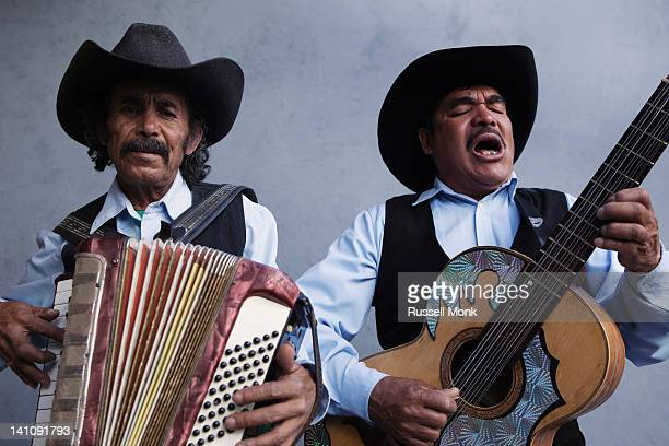 Two Mexican musicians singing
