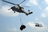 Indian Ocean, October 21, 2009 - Two MH-60S Sea Hawk helicopters assigned to the Wildcards of Helicopter Sea Combat Squadron 23 transfer cargo during a vertical replenishment with the Military Sealift