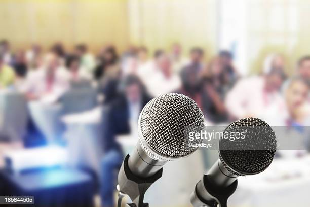 Two microphones wait for the speaker at a press conference