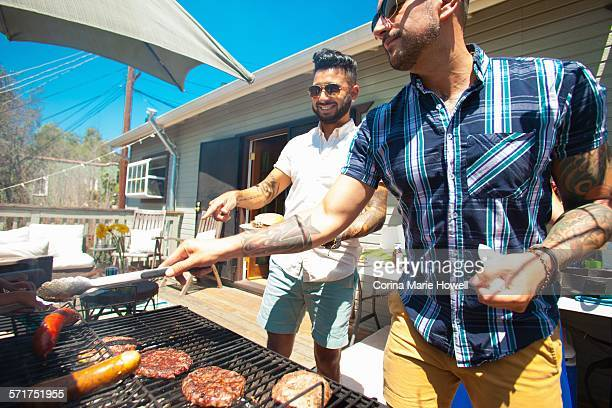 Two mid adult brothers barbecuing in garden