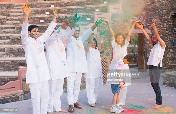 Two mid adult couples and a young couple with a boy celebrating holi