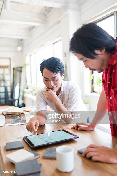 Two mid adult men lookin at a digital tablet