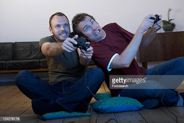 Two mid adult men playing video games