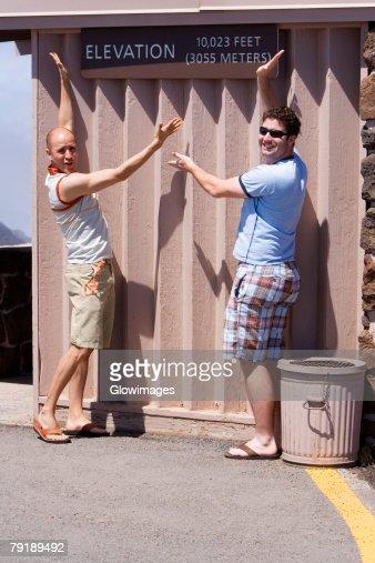 Two mid adult men posing against a wall, Haleakala National Park, Maui, Hawaii Islands, USA : Stock Photo