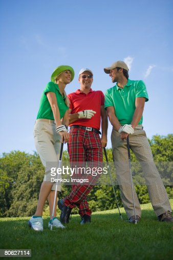 Two mid adult men standing with a mid adult woman on a golf course and holding golf clubs : Foto de stock