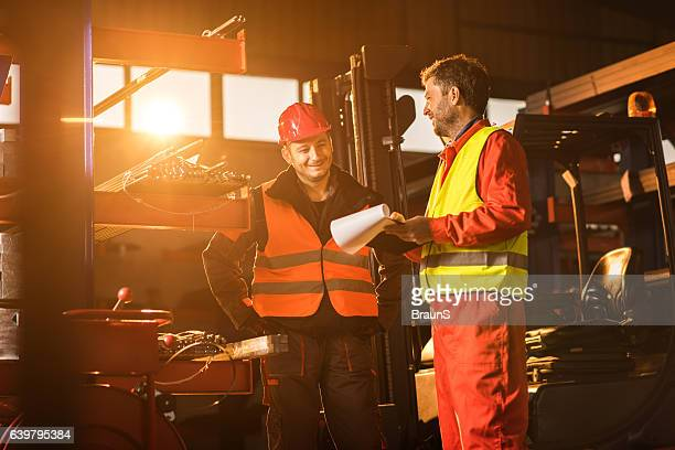 Two mid adult metal workers communicating in aluminum mill.