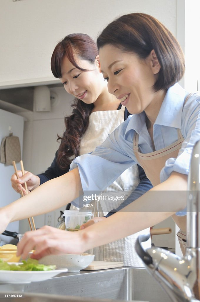 Two mid adult women cooking in the kitchen : Stock Photo