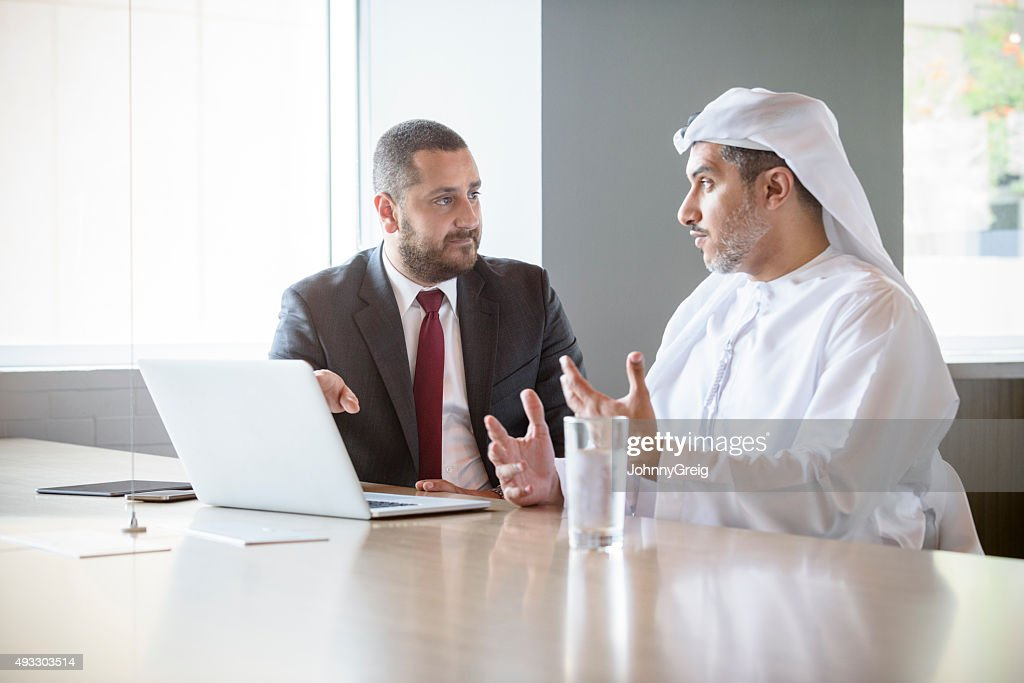 Two Middle Eastern businessmen in meeting using laptop