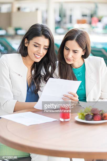 Two Middle Eastern Businesswomen Reviewing Documents During Outdoor Business Lunch