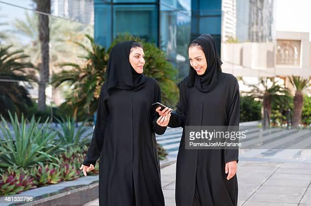 Two Middle Eastern Women Friends Walking Outside Modern Office Buildings