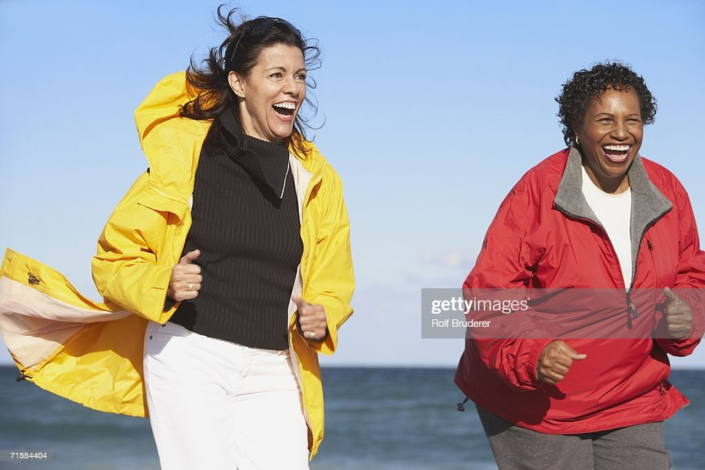 Two middle-aged women laughing outdoors : Stock Photo
