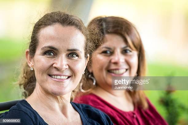 Dos mujeres de edad madura posando sonriente