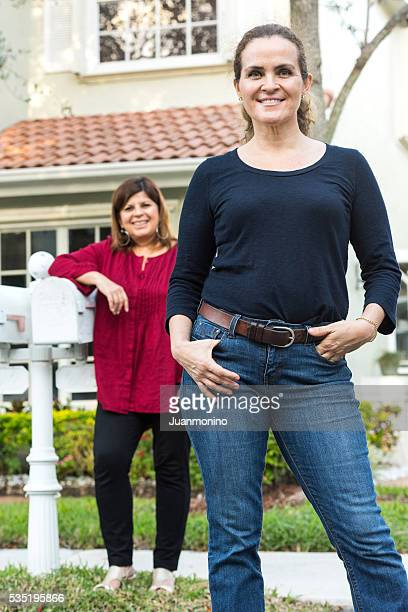 Two middle-aged women posing smiling