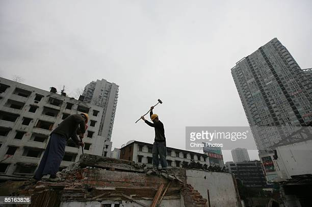 Two migrant workers dismantle a wall atop housing ruins on March 1 2009 in Chongqing China China is facing a difficult employment situation in 2009...