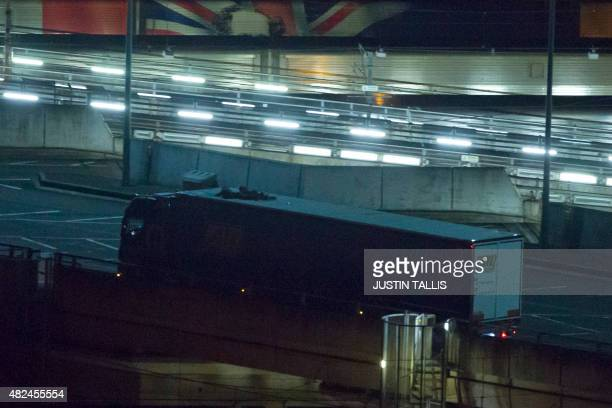 Two migrants cling to the roof of a freight truck as they arrive at the Eurotunnel terminal in the English city of Folkestone on July 31 after...