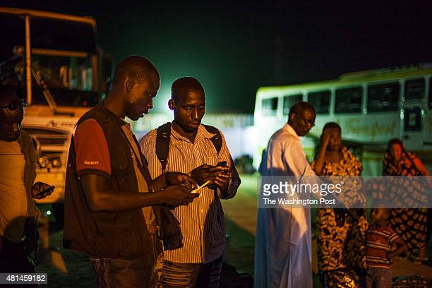 AGADEZ NIGER Two migrants from Burkina Faso exchange telephone numbers upon arriving to Agadez Niger This is the final stop of commercial buses The...