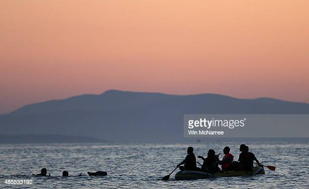 Two migrants from Syria are assisted by their friends as they swim the final 50 yards of their journey before arriving on the beach on the island of...