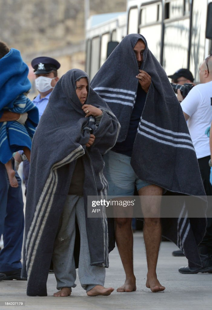 Two migrants wrapped in blankets arrive at Hay Wharf in Valletta after being rescued by the Armed forces of Malta on October 12, 2013. More than 140 survivors, plucked from the sea after their overloaded boat sank in the latest deadly migrant tragedy to hit the Mediterranean, arrived in Malta. The sinking killed more than 30, most of them women and children, when the boat packed with people desperate to reach European shores went down off Malta near the Italian island of Lampedusa, according to officials.